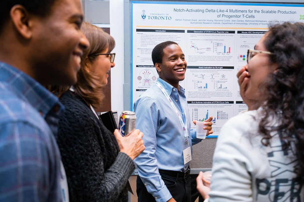 Four people stand in front of a research poster presentation.