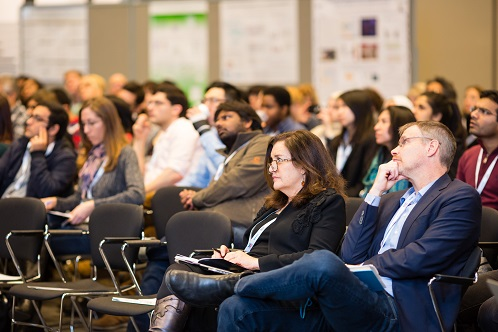 Photo of crowd of people listening to a symposium presentation.