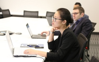Jessica Yu and Anton Neschadim sit at a table during a team meeting in November 2016