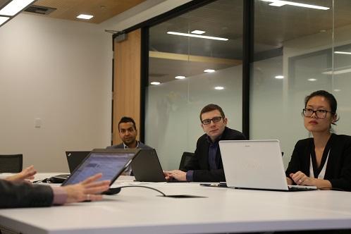 Arif Aziz, Anton Neschadim and Jessica Yu sit at a table at a team meeting in November 2016.