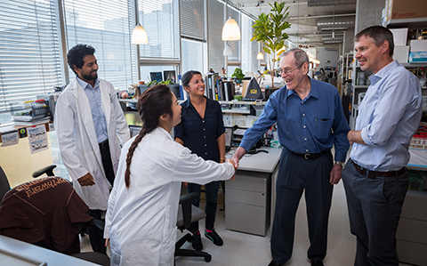 Photo of stem cell pioneer James Till meeting Shreya Shukla and two fellow graduate students during a tour of Peter Zandstra's lab.