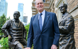 Photo of James Till with a new permanent sculpture depicting him and Ernest McCulloch, who proved the existence of stem cells in the 1960s.