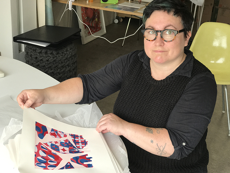 Artist Michelle Forsyth shows the screen print she created for the Medicine by Design Global Speaker Series.