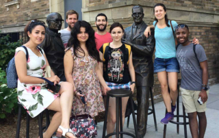 2018 Summer by Design participants pose with statues of Ernest McCulloch and James Till outside MaRS building in Toronto.