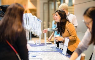 Volunteers help attendees find their name tags at the registration table.