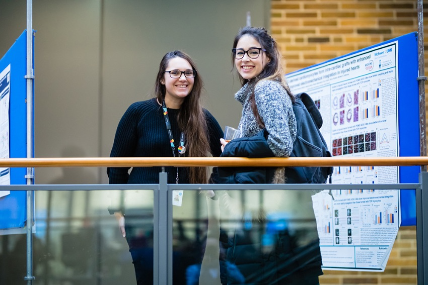 Two trainees stand by their research posters at the 2019 Medicine by Design symposium.
